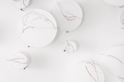 Untitled (sample), installation view, embroidery hoops with Japanese mending tissue, cotton-rag paper and gouache, cotton thread, threaded steel rods, wire grips, dimensions range from 10cm to 40cm diameter, 2014